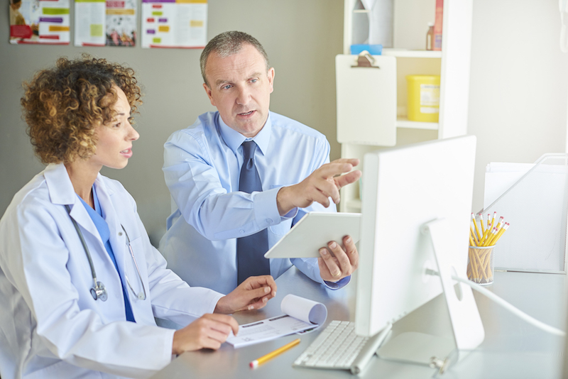 a medical salesman or administrator is sitting with a female doctor and running through a presentation . He is explaining something and referring to the computer screen in front of them on the desk.