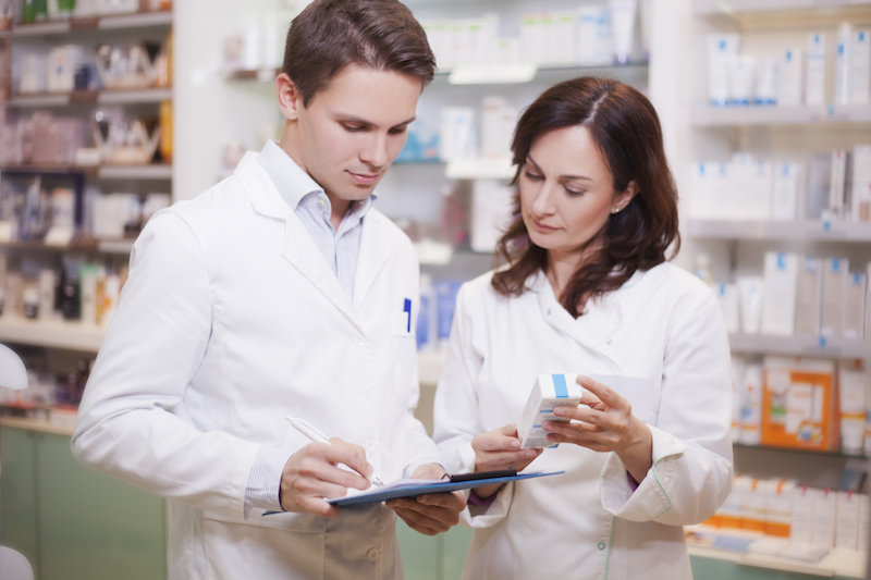 Male and female pharmacists at work