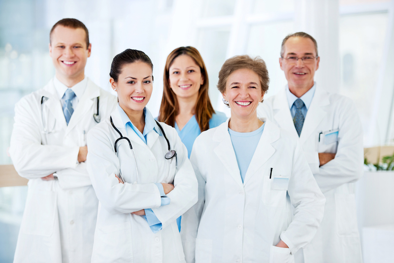 Group of cheerful doctors standing together and looking at camera.